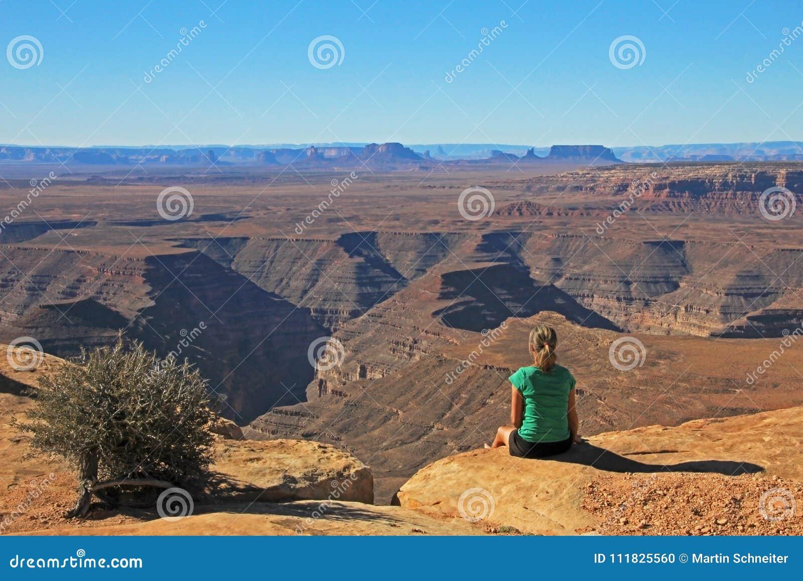 Nette Frau mit dem langen Haar, das am Rand der Klippe an Muley-Punkt sitzt und das overwiev zum Goosenecks-Zustand genießt