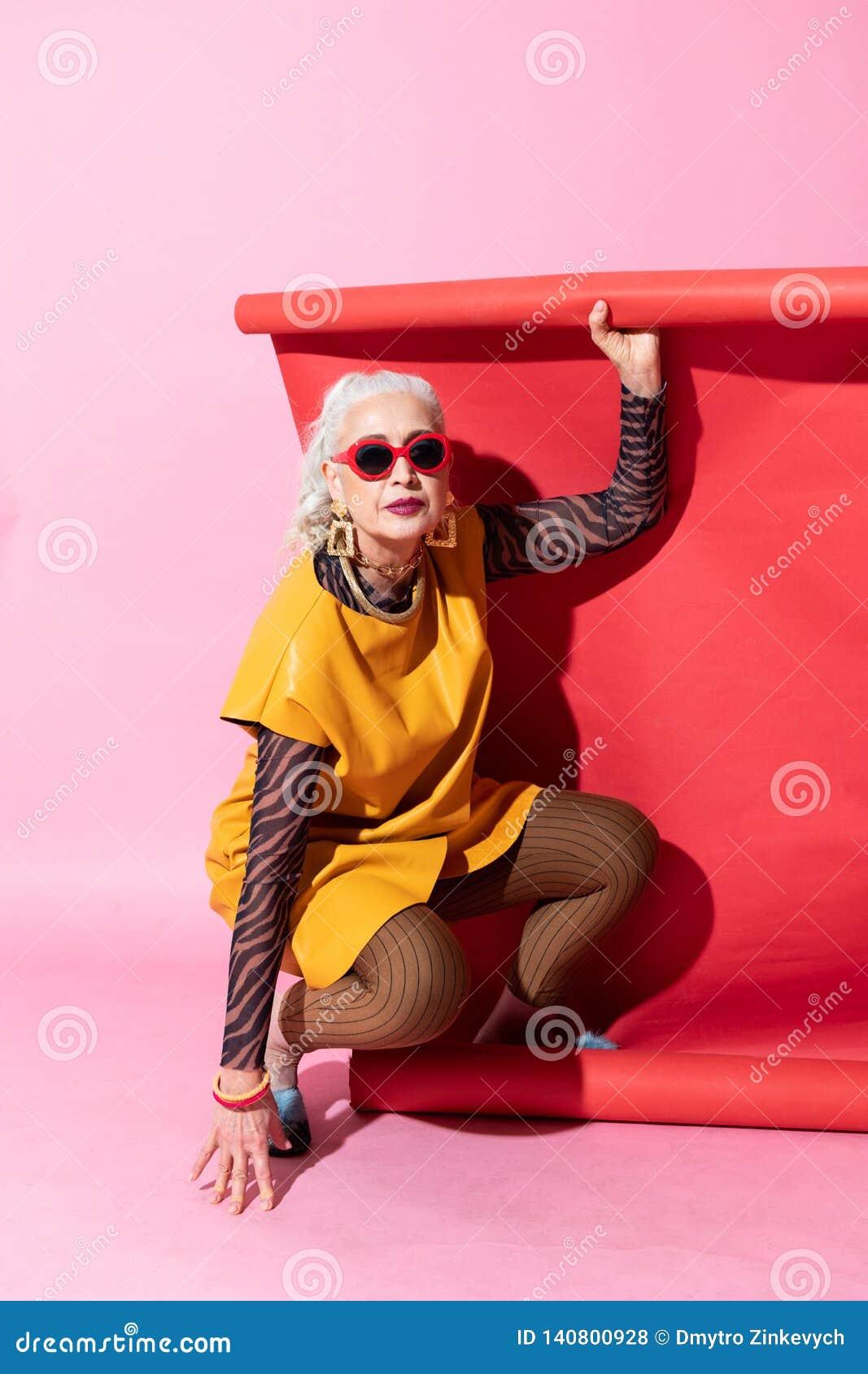 Nette gealterte weibliche Person, die auf Kamera aufwirft