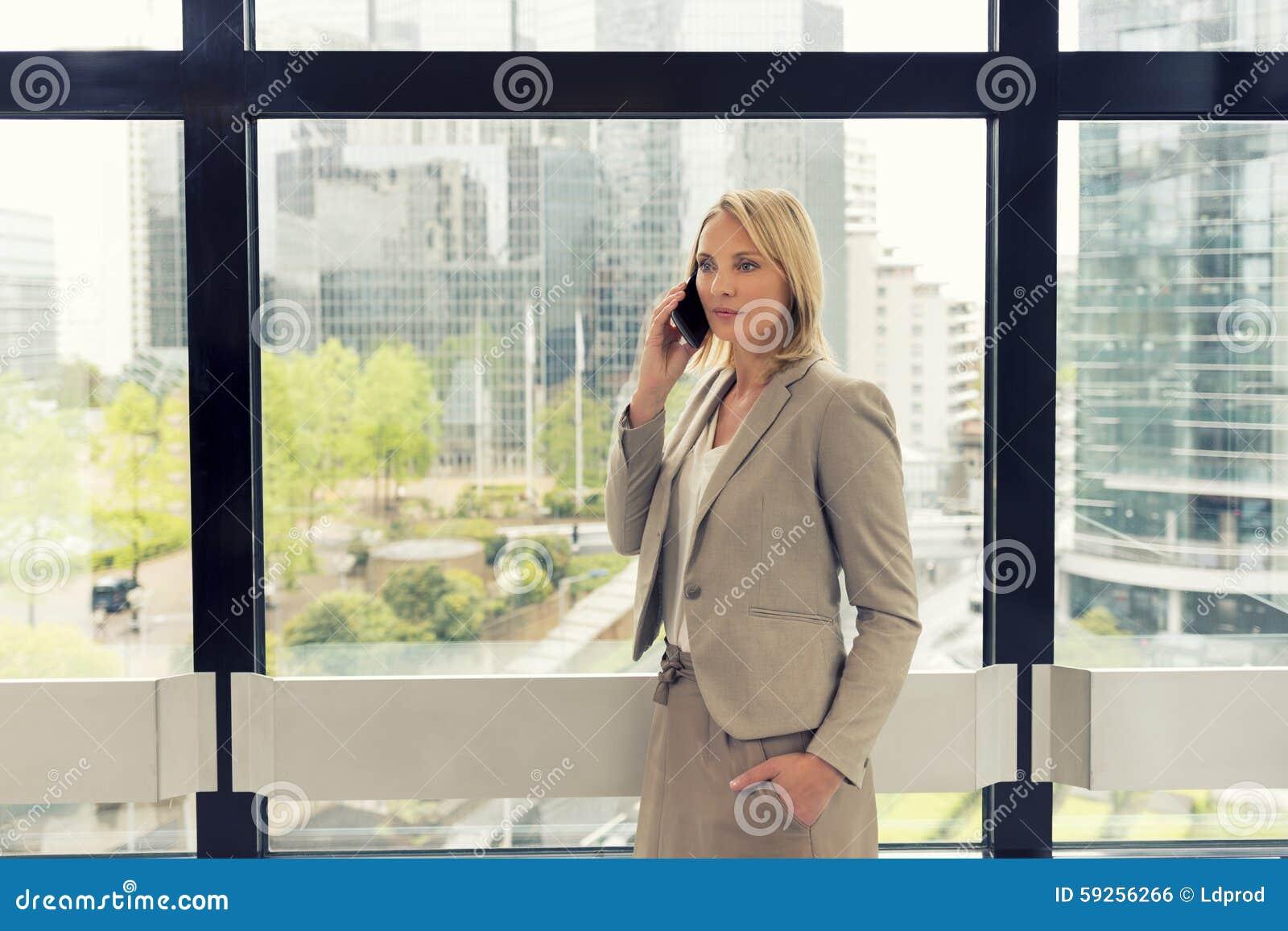 Nette Geschäftsfrau am Handy im modernen Büro Buildi