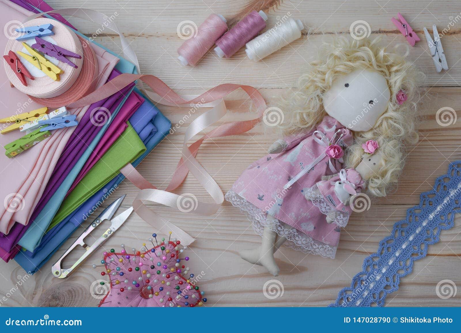 Nette handgemachte Puppe auf einem Holztisch mit bunten Geweben, gestrickter Spitze, Pastellbändern und nähenden Möbeln