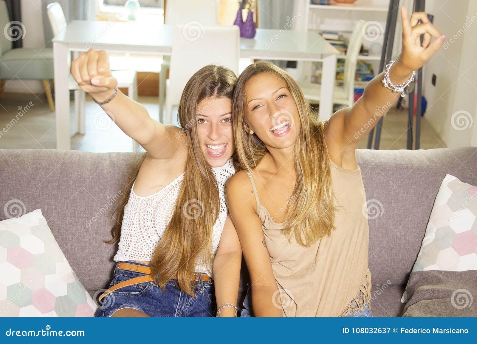 Nette Jugendliche, die Videospiel mit glücklicher lächelnder schauender Kameranahaufnahme der Konsole spielen