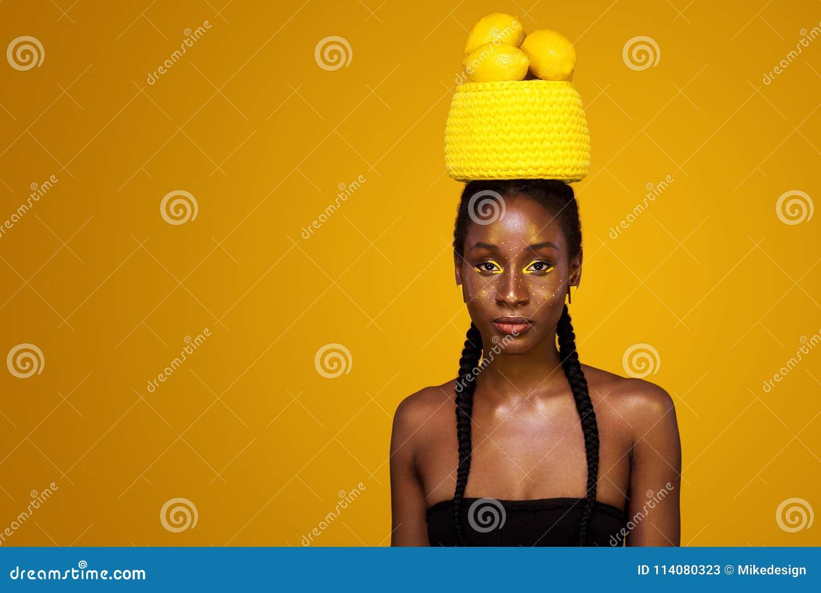 Nette junge afrikanische Frau mit gelbem Make-up auf ihren Augen Weibliches Modell gegen gelben Hintergrund mit gelben Zitronen