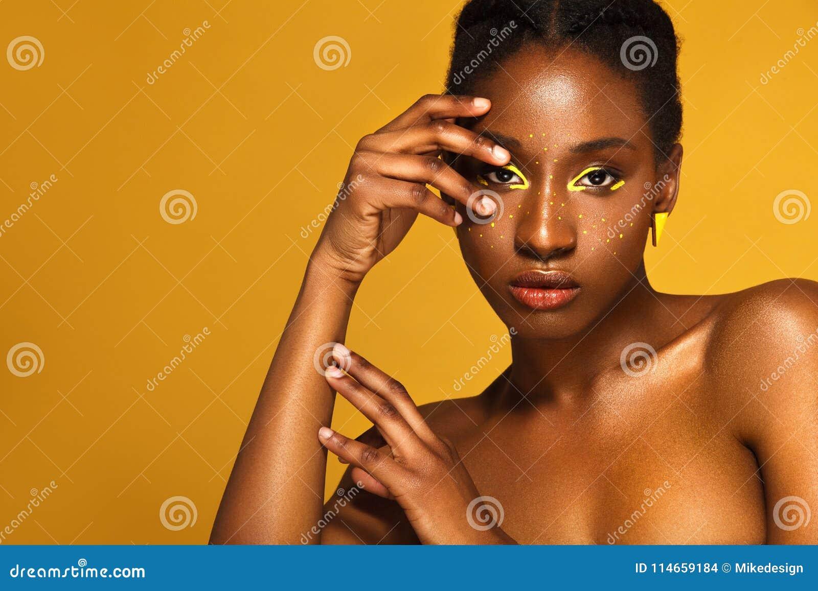 Nette junge afrikanische Frau mit gelbem Make-up auf ihren Augen Weibliches vorbildliches Lachen gegen gelben Hintergrund