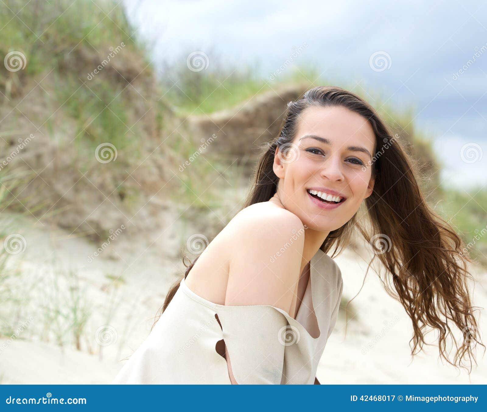 Nette junge Frau, die draußen lacht