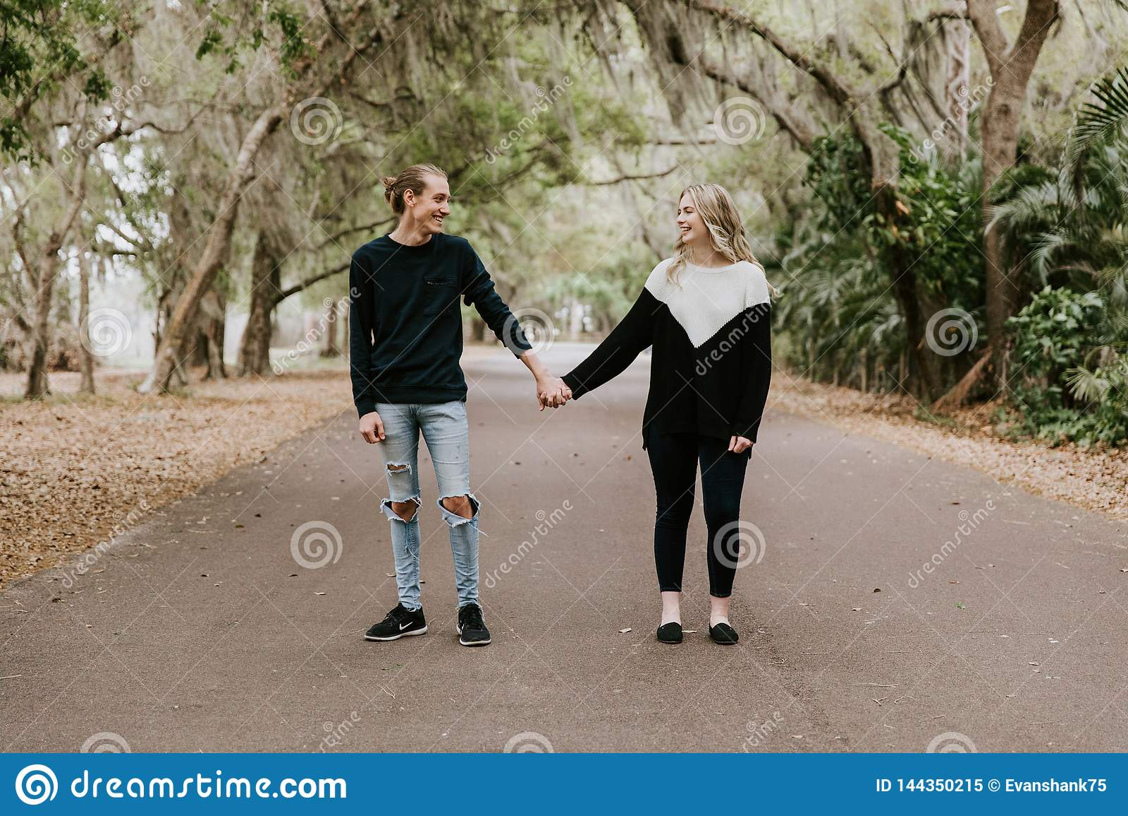 Nette junge glückliche liebevolle Paare, die hinunter eine alte verlassene Straße mit dem moosigen Eichen-Überhängen gehen