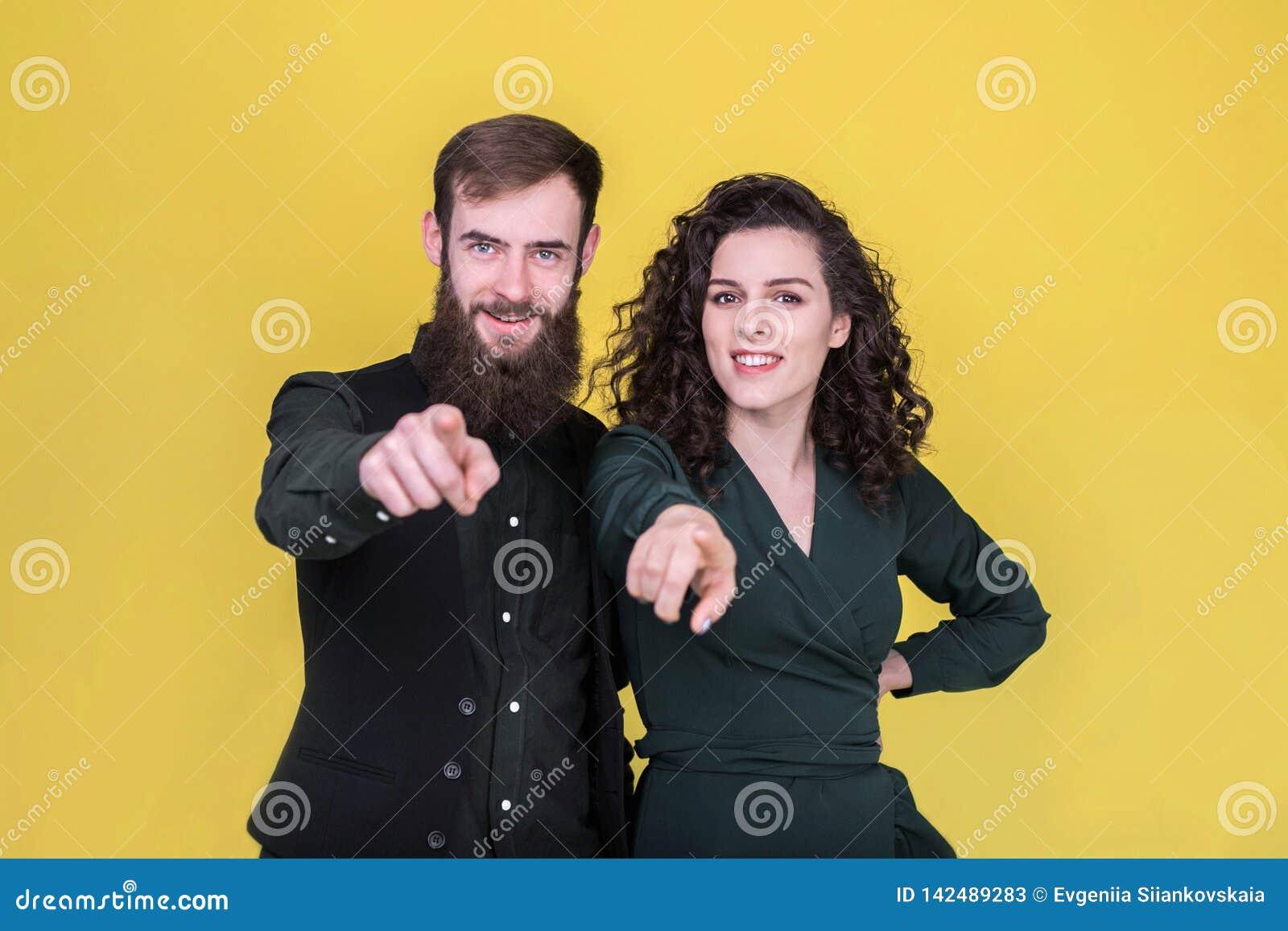 Nette junge Leute, die Finger auf Kamera zeigen