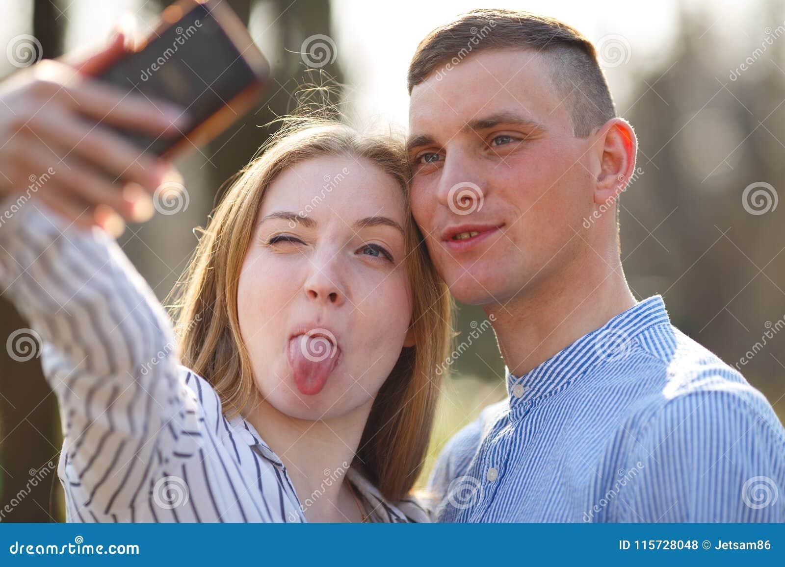 Nette junge Paare machen Gesichter und nehmen selfie draußen Jugend, bezüglich
