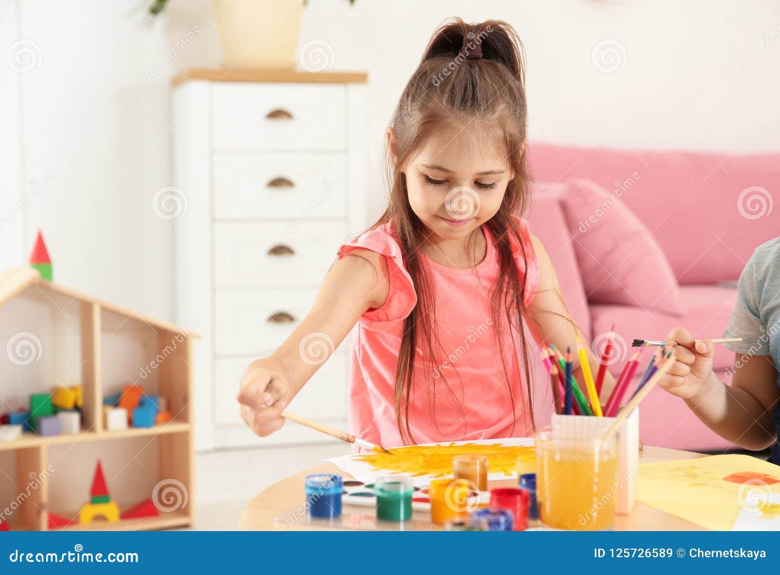 Nette kleine Kinder, die bei Tisch malen