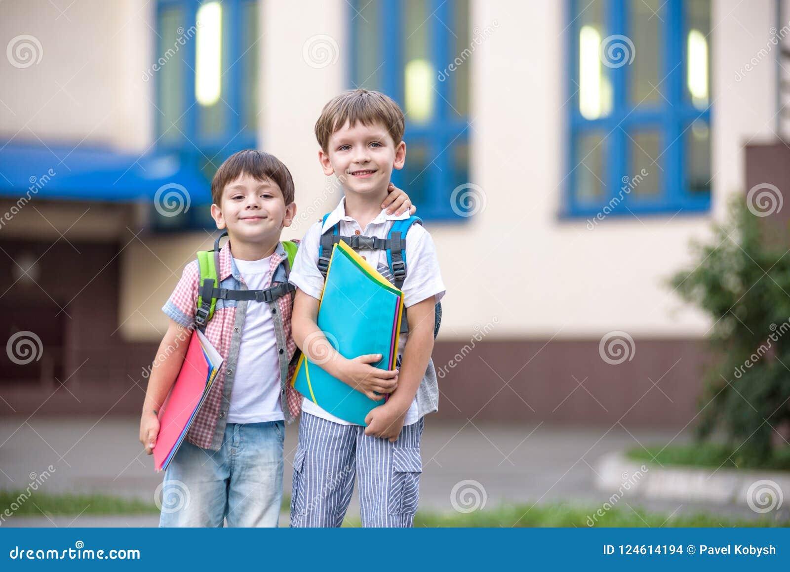 Nette kleine Schüler sprechen lebhaft auf dem Schulhof Chil