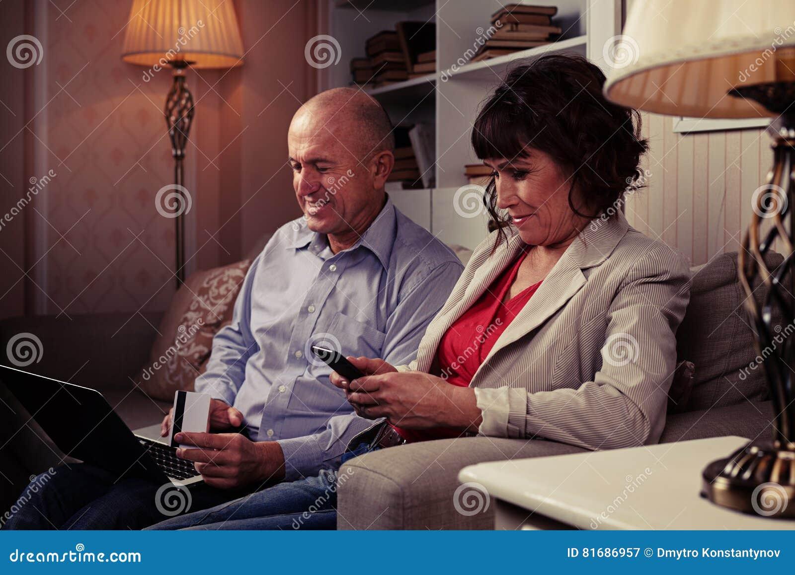 Nette Leute, die auf dem Sofa und dem Lächeln sitzen