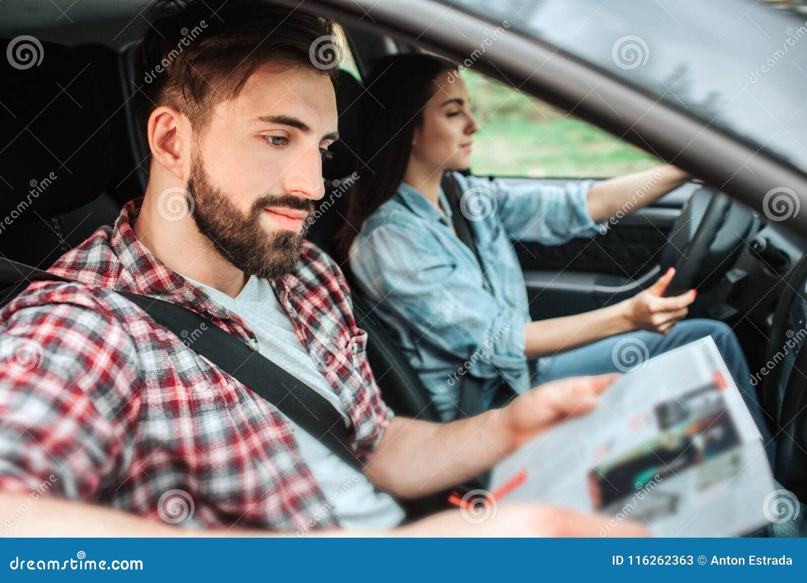 Nette Leute reiten in Auto Mädchen fährt Maschine Kerl sitzt außer ihrem und liest ein Buch Sie sind