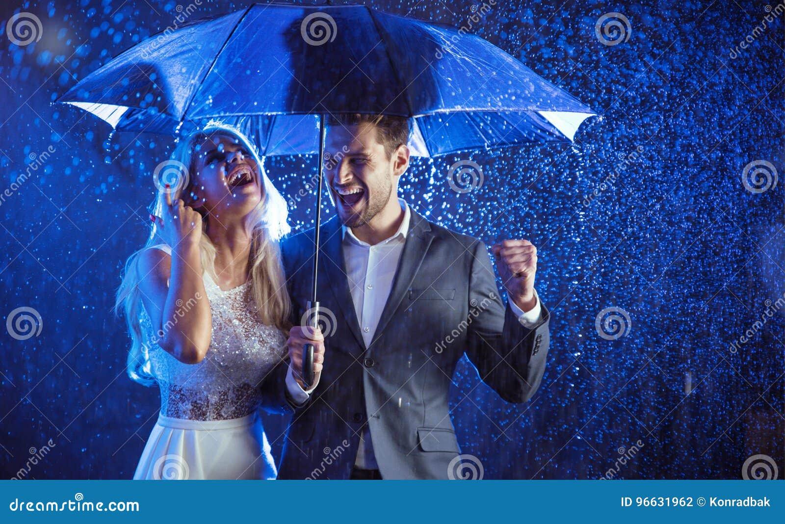 Nette Paare, die den Sommerregen genießen