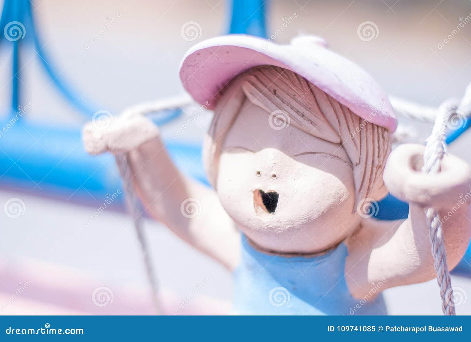 Nette rosa keramische Mädchenpuppe spielt Seilschwingen auf dem Blau ich