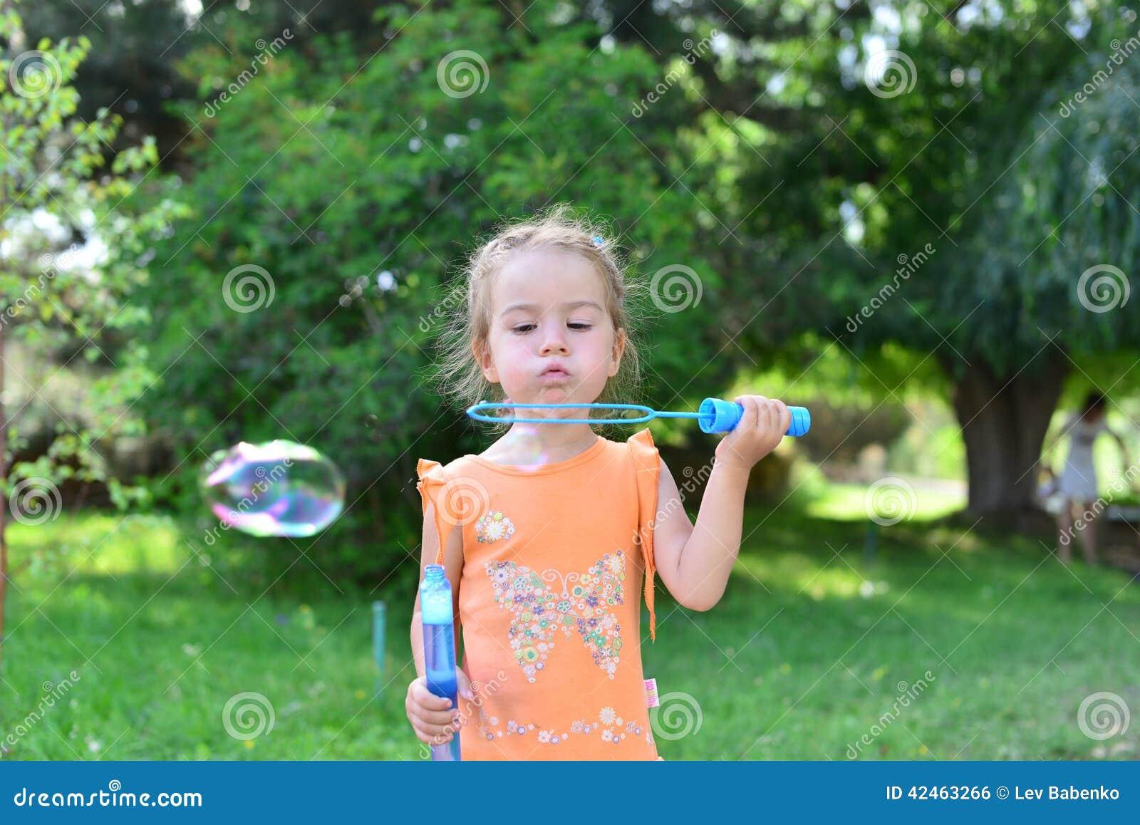 Nette Schlagseifenblasen des kleinen Mädchens in der Natur