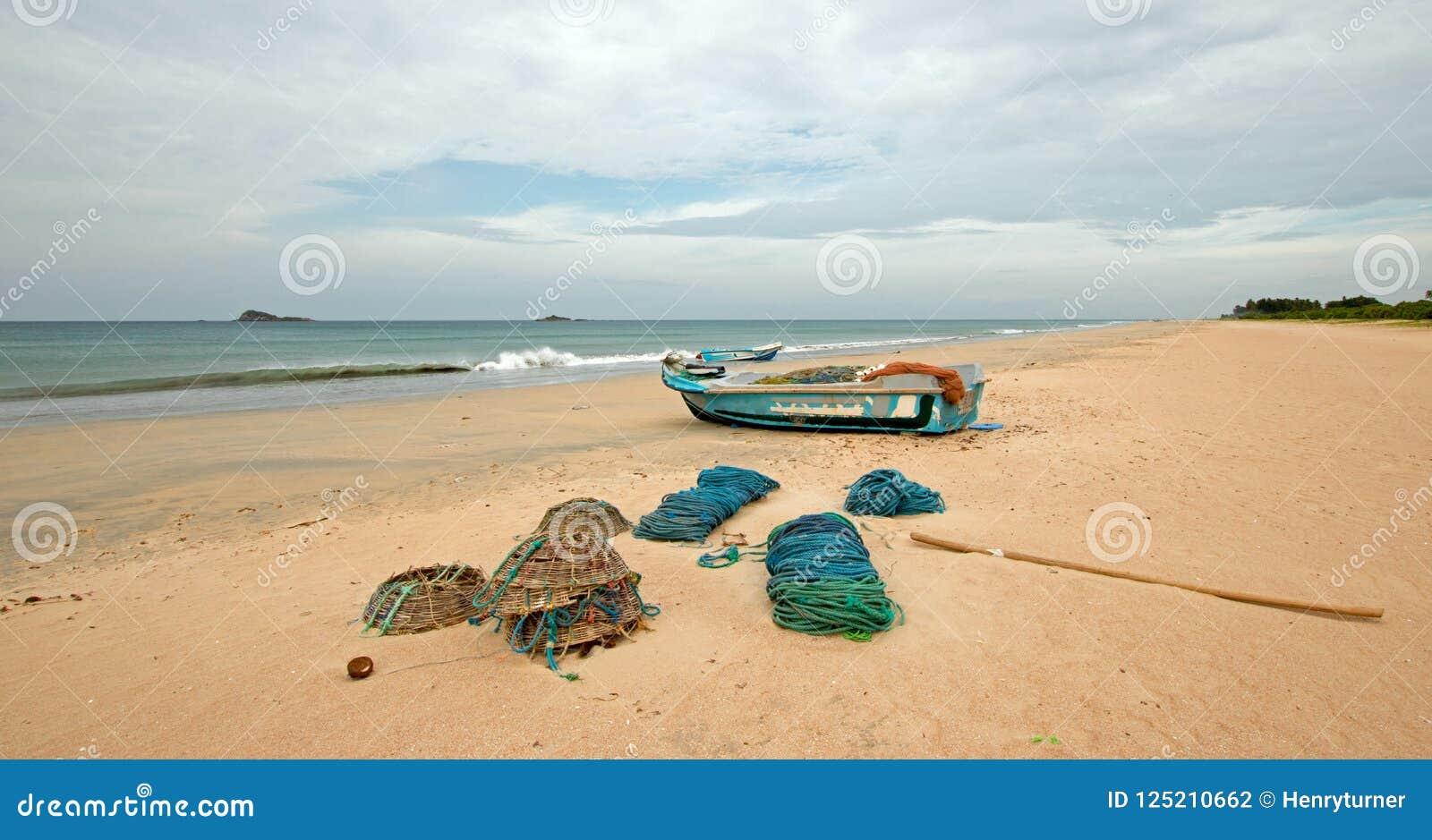 Netten, vallen, manden, en kabels naast vissersboot op Nilaveli-strand in Trincomalee Sri Lanka