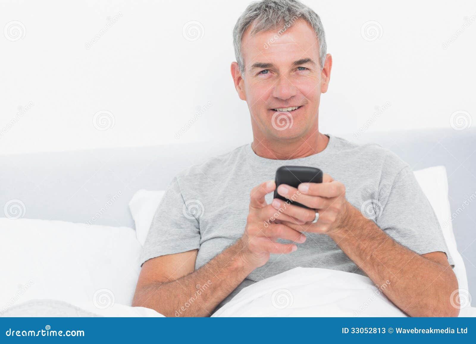 netter grauer behaarter mann der einen text im bett sendet stockbild bild 33052813. Black Bedroom Furniture Sets. Home Design Ideas