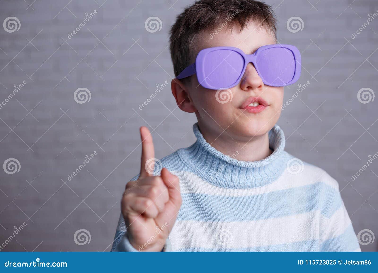 Netter Junge in der violetten Sonnenbrille mit undurchsichtigen Linsen aufwärts zeigend