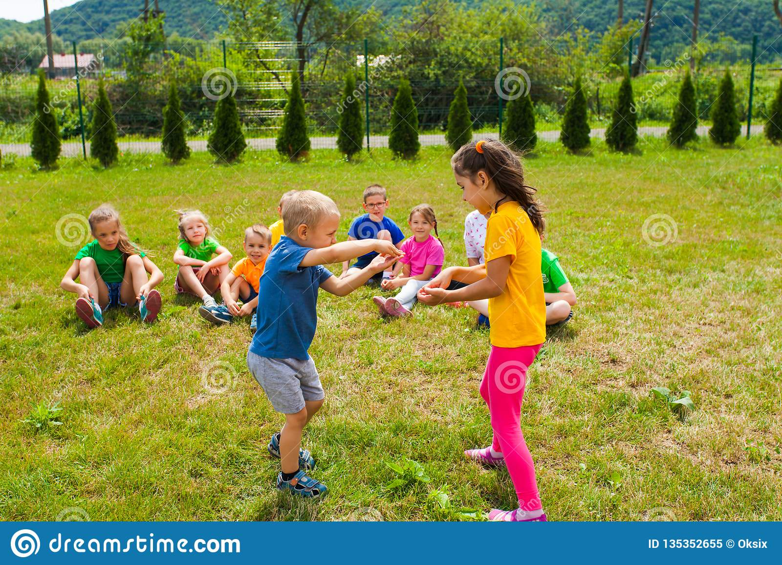 Netter Junge und Mädchen, die vor ihren Freunden spielt