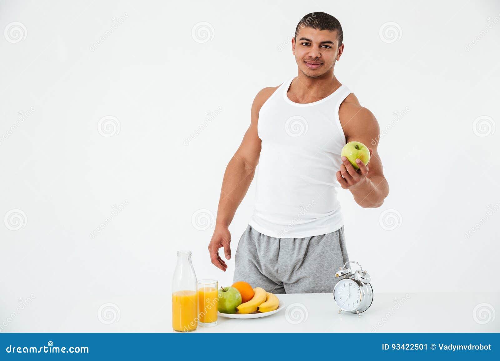 Netter junger Sportler, der Apfel hält Betrachten der Kamera