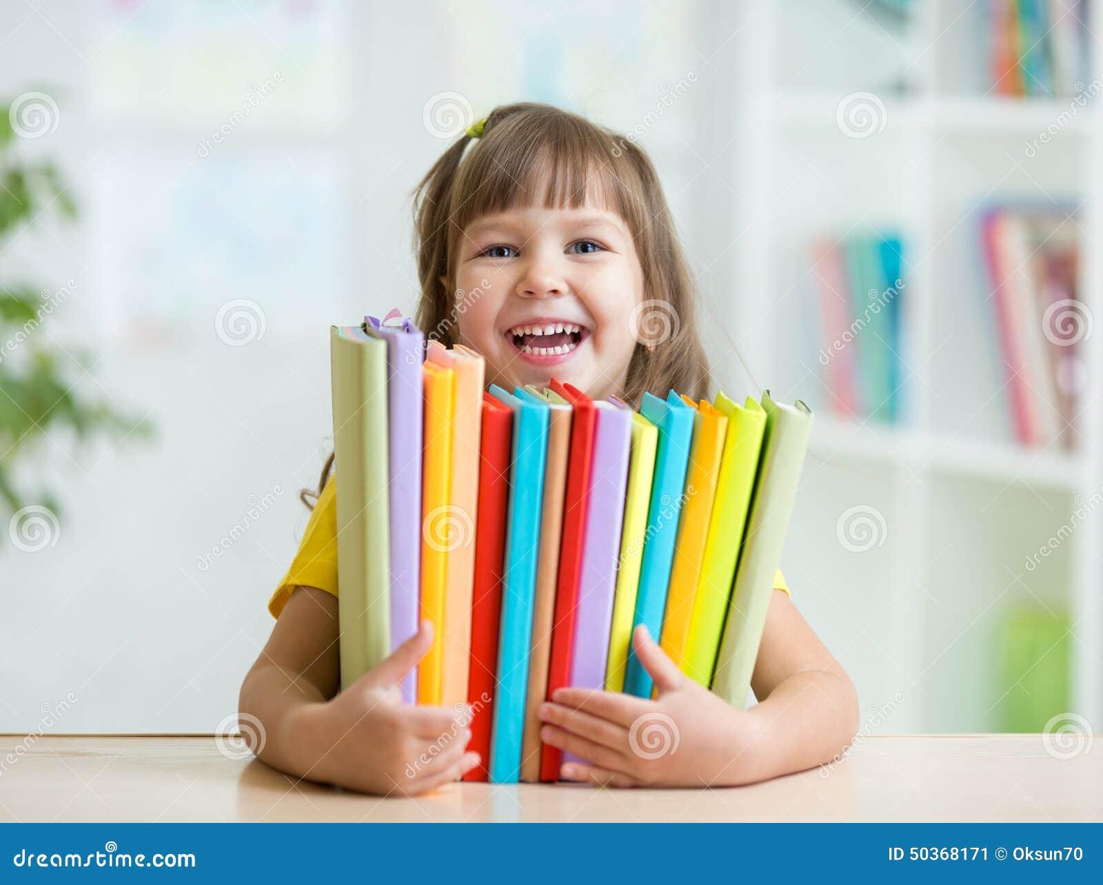 Netter Kindermädchenvorschüler mit den Büchern Innen
