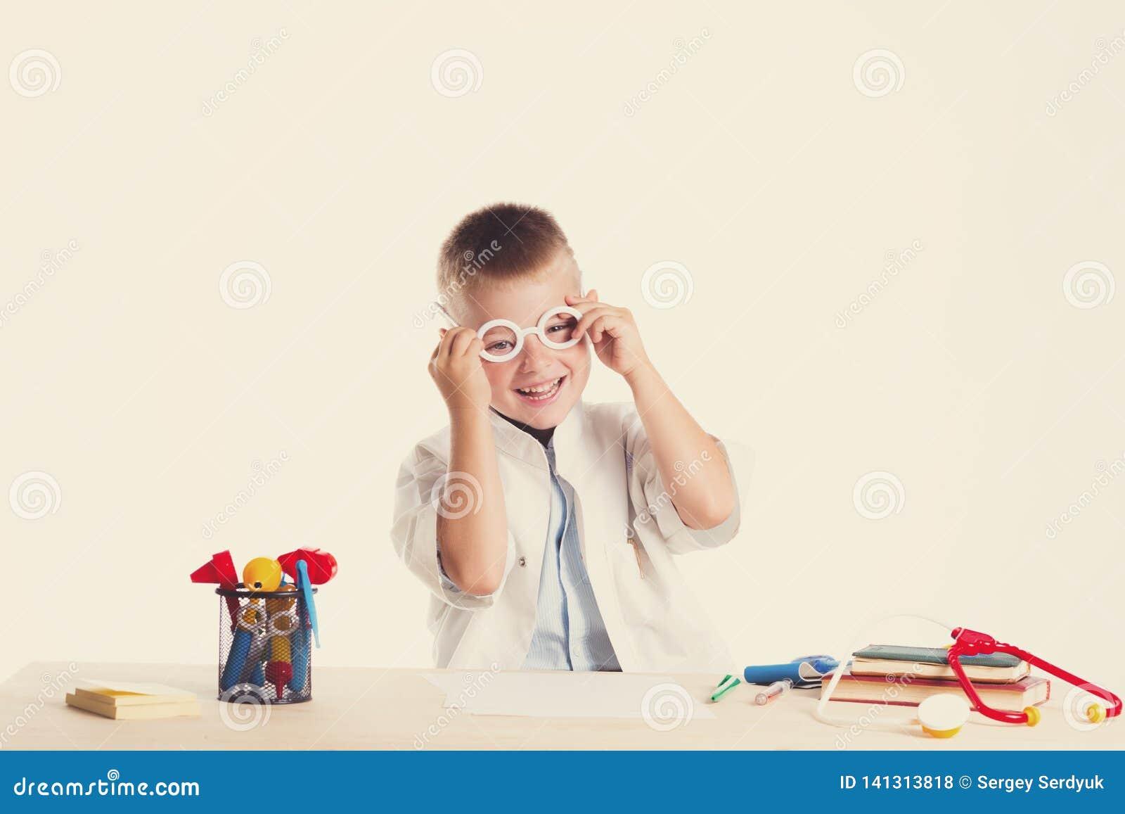 Netter kleiner Doktorjunge mit Lächeln auf dem Gesicht, das an seinem Schreibtisch auf weißem Hintergrund sitzt Intelligente Kind