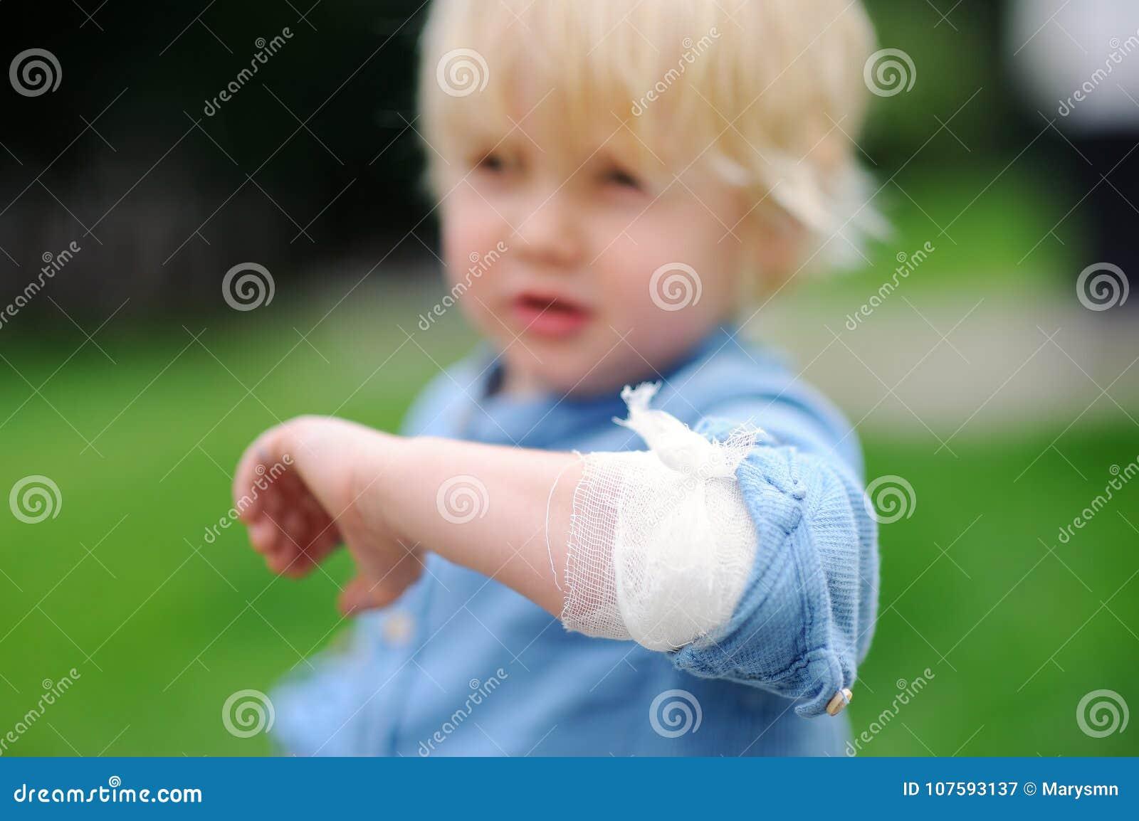 Netter kleiner Junge, der auf seinem Ellbogen mit angewandtem Verband schaut