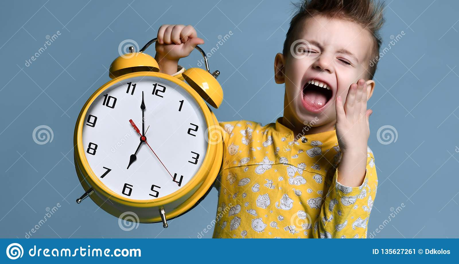 Netter kleiner Junge mit dem Wecker, lokalisiert auf Blau Lustiges Kind, das auf Wecker um 7 Uhr auf Morgen zeigt