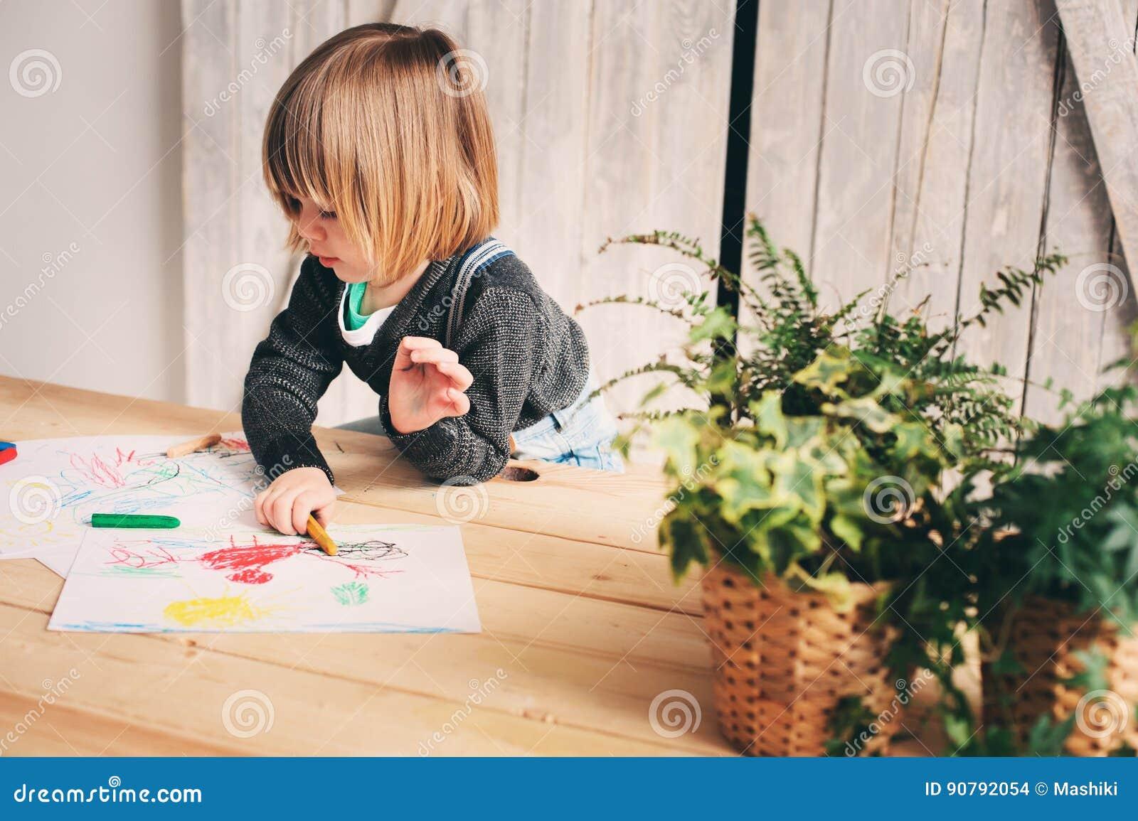 Netter Kleinkindjunge, der zu Hause zeichnet
