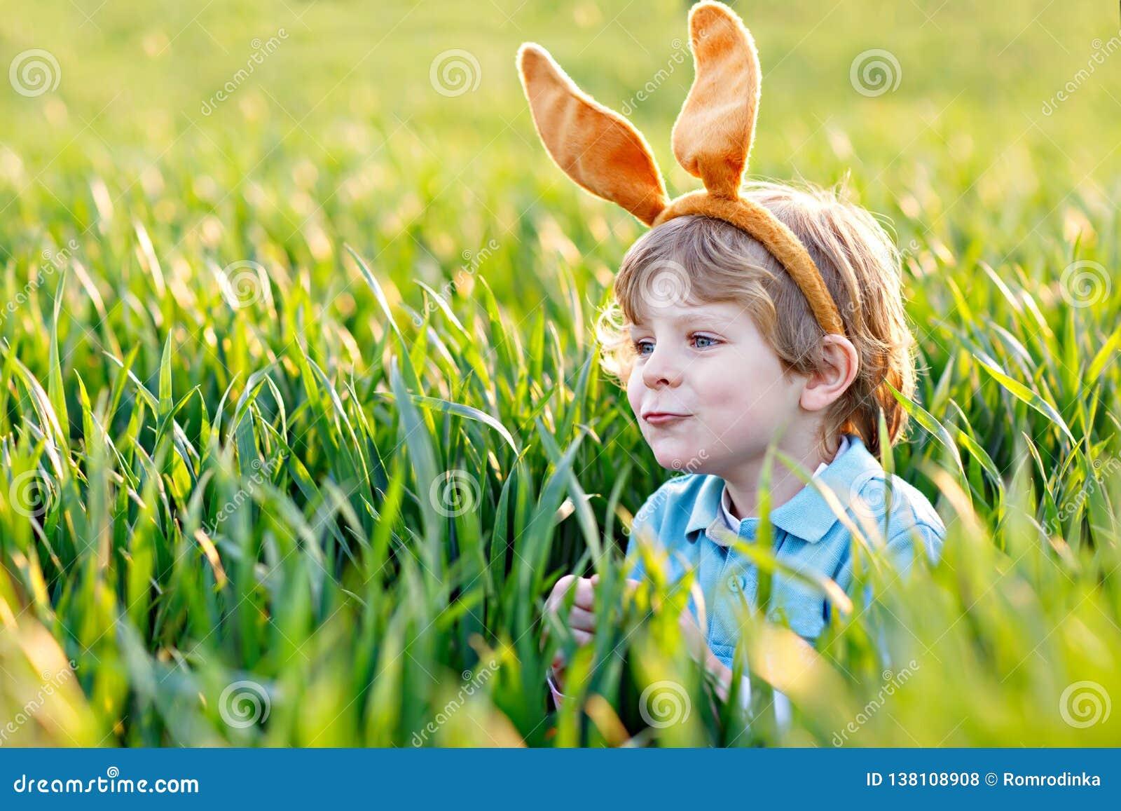 Netter Kleinkindjunge mit den Häschenohren, die Spaß mit traditionellen Ostereiern haben, jagen am warmen sonnigen Tag, draußen