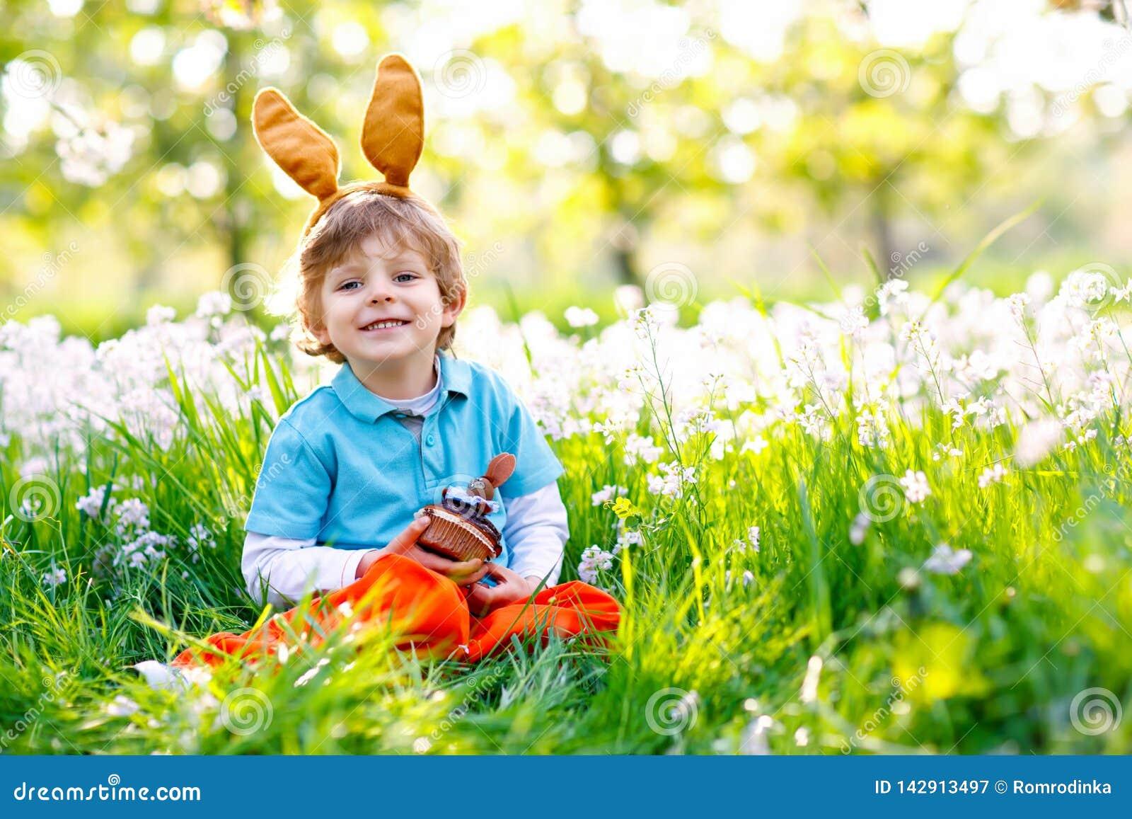 Netter Kleinkindjunge mit den Osterhasenohren das glückliche Kind des traditionellen Festes feiernd, das an Schokoladenkuchen des