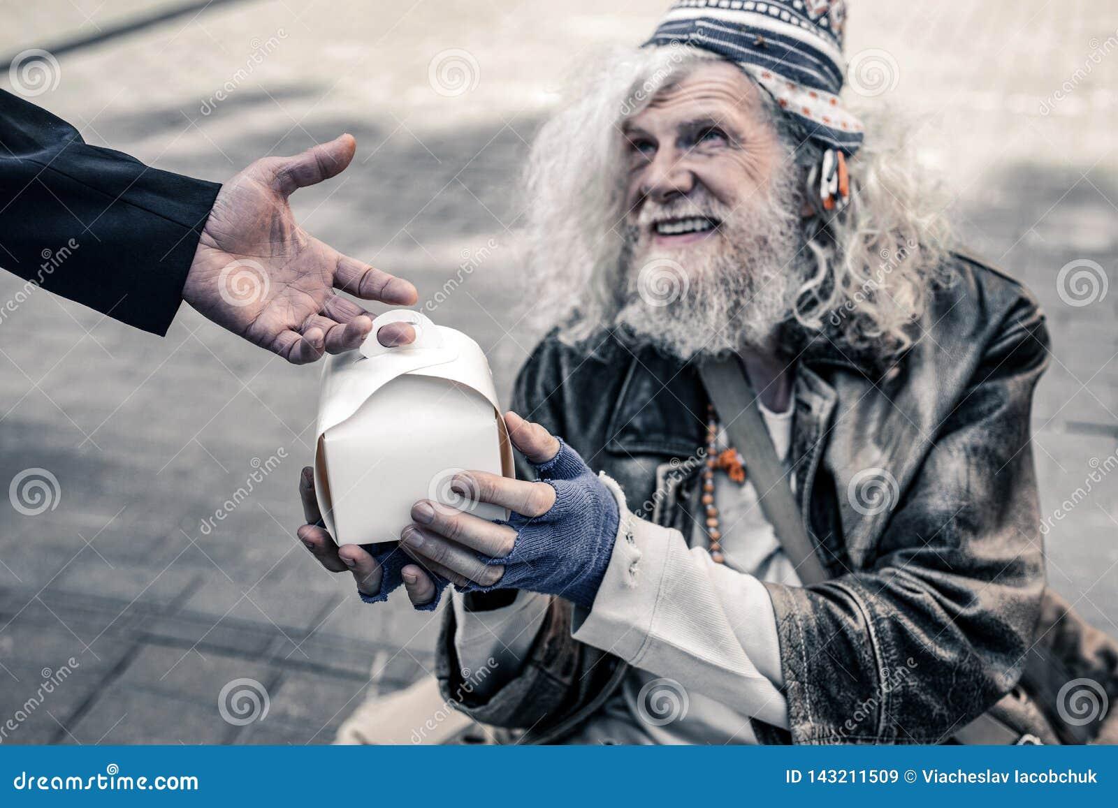Netter langhaariger alter Mann, der auf der Straße lebt und Kasten mit Nahrung hält