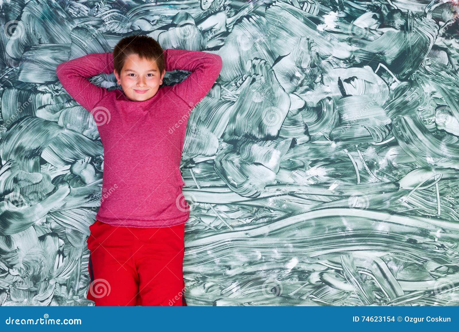 Netter Tweenjunge, der auf großer grüner Malerei sich entspannt