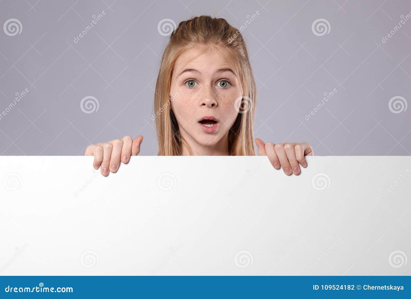 Nettes überraschtes Mädchen mit leerem Werbungsbrett