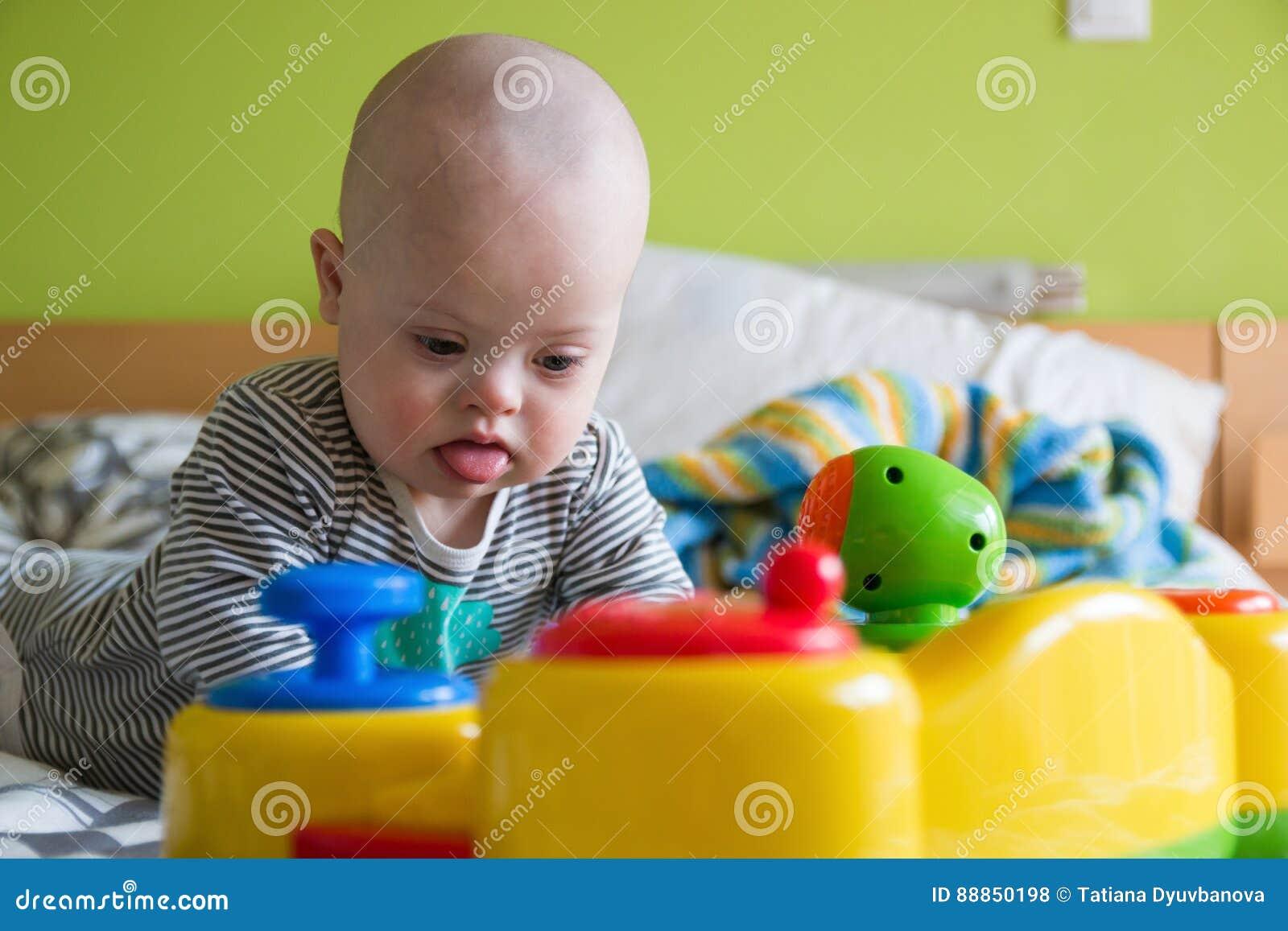 Nettes baby mit down syndrom das spielzeug spielt