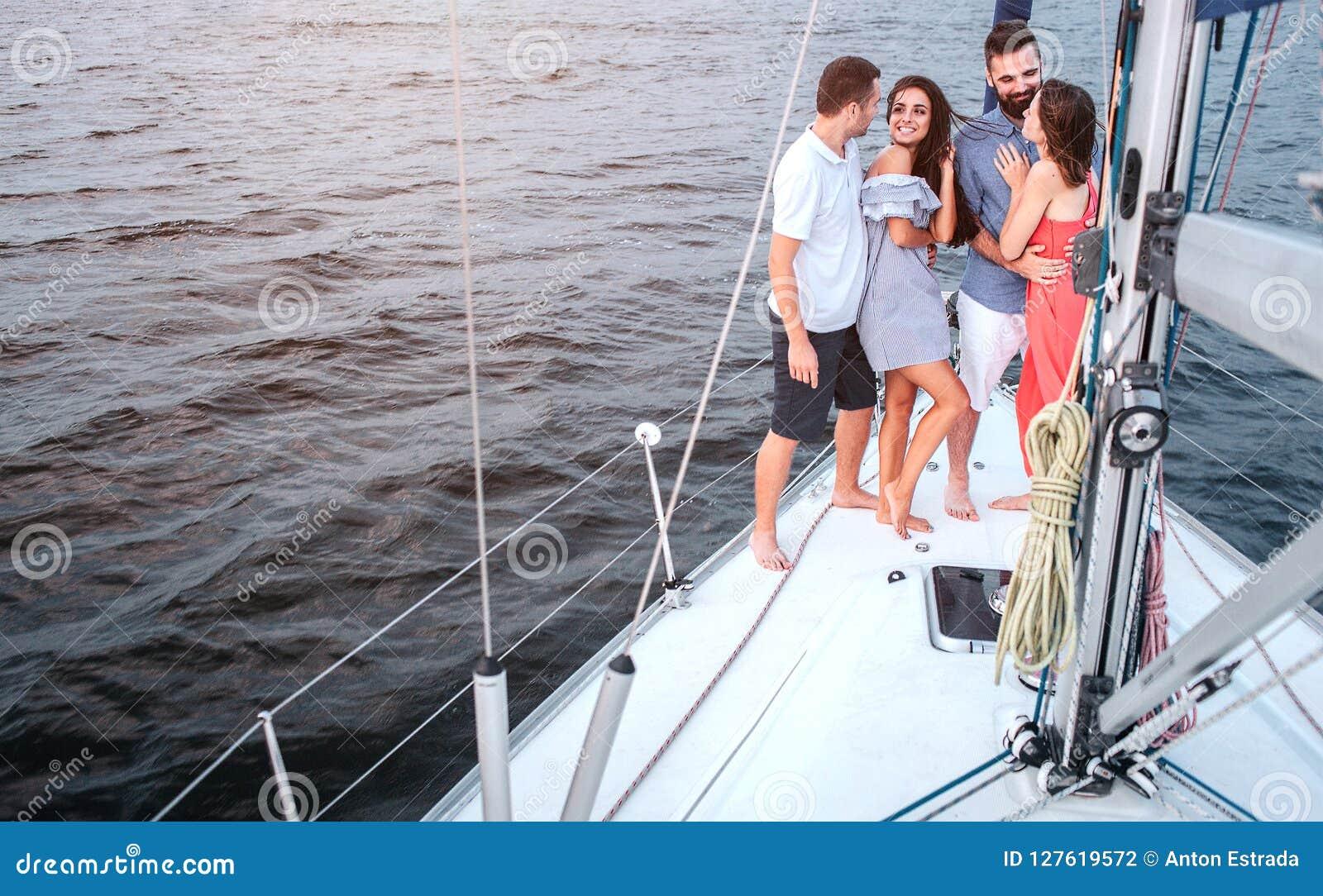 Nettes Bild von vier Leuten, die auf Yacht stehen Brunette betrachtet Kerl Sie lächelt Er umfasst sie Eine anderen Paare
