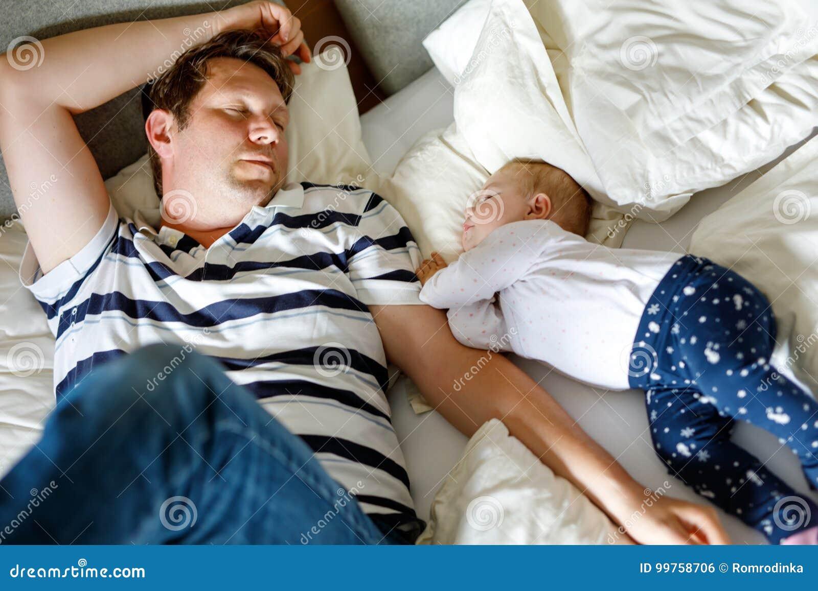Nettes entzückendes Baby von 6 Monaten und von ihrem Vaterschlafen ruhig im Bett zu Hause