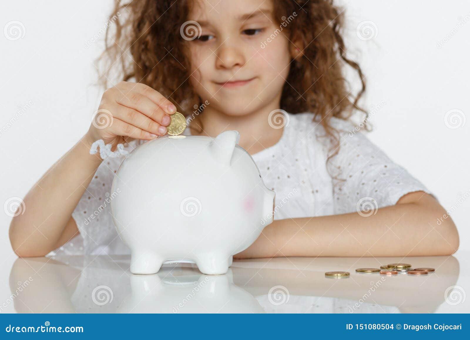 Nettes gelocktes kleines Mädchen, das Münze in großes weißes Sparschwein, über weißem Hintergrund setzt Pädagogisches, Rettungsge