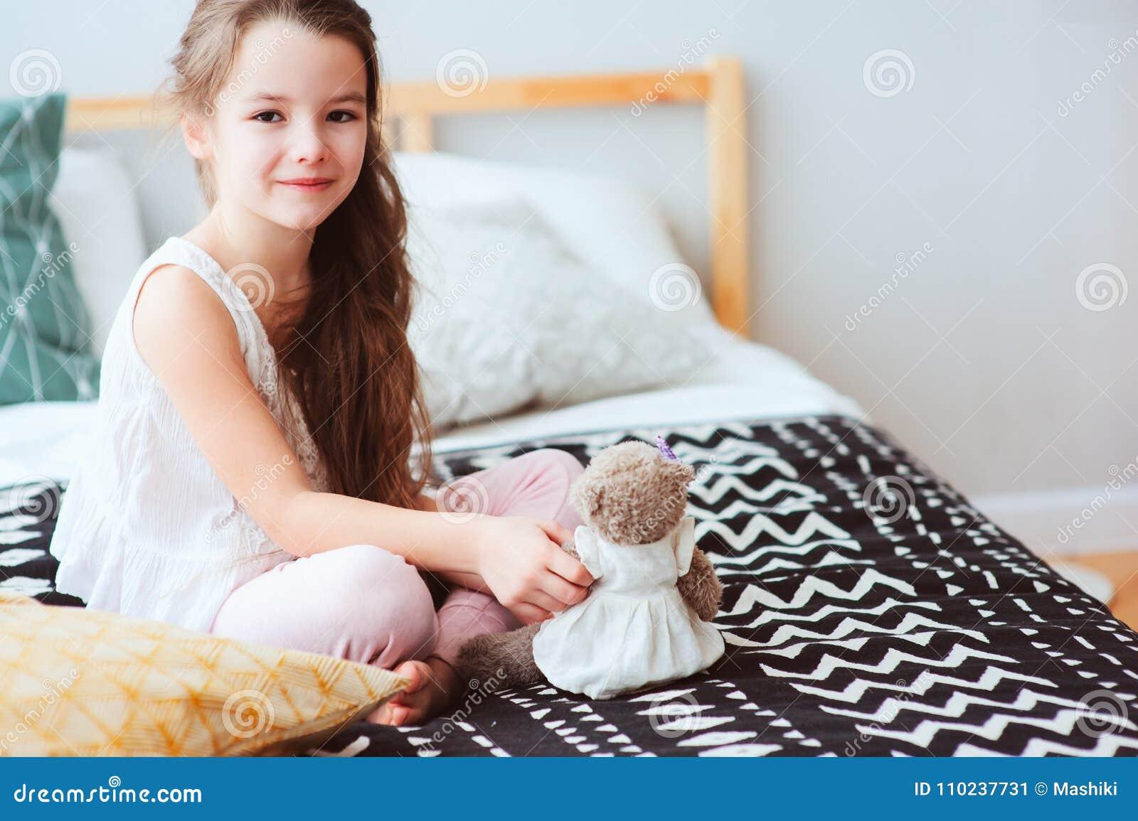 Nettes glückliches Kindermädchen, das sich zu Hause auf dem Bett in ihrem Raum am frühen Morgen entspannt