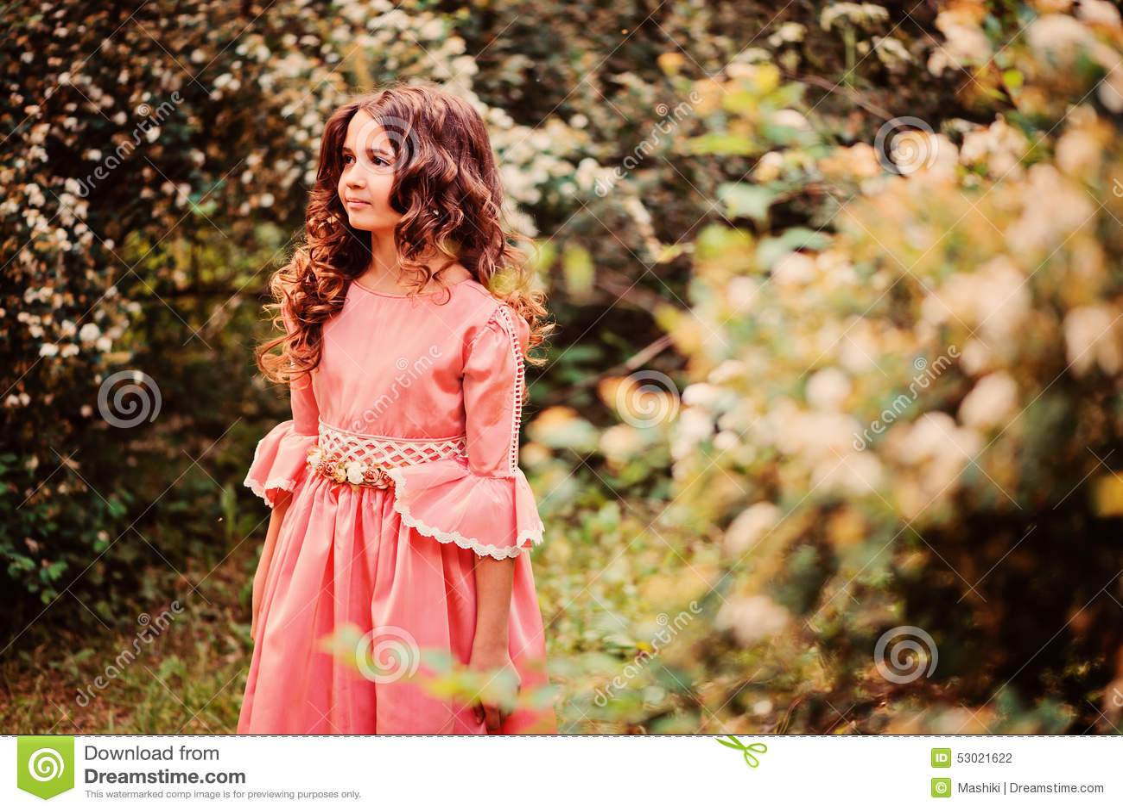 Nettes glückliches Kindermädchen in Märchenprinzessinkleid auf dem Weg im Sommer