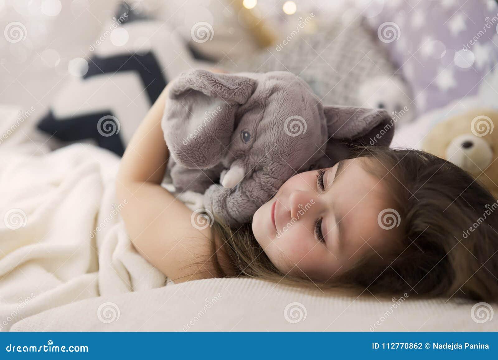 Nettes glückliches kleines Mädchen, das herein schlafen und träumen und Bett, das ihr Spielzeug umarmt Schließen Sie herauf Foto