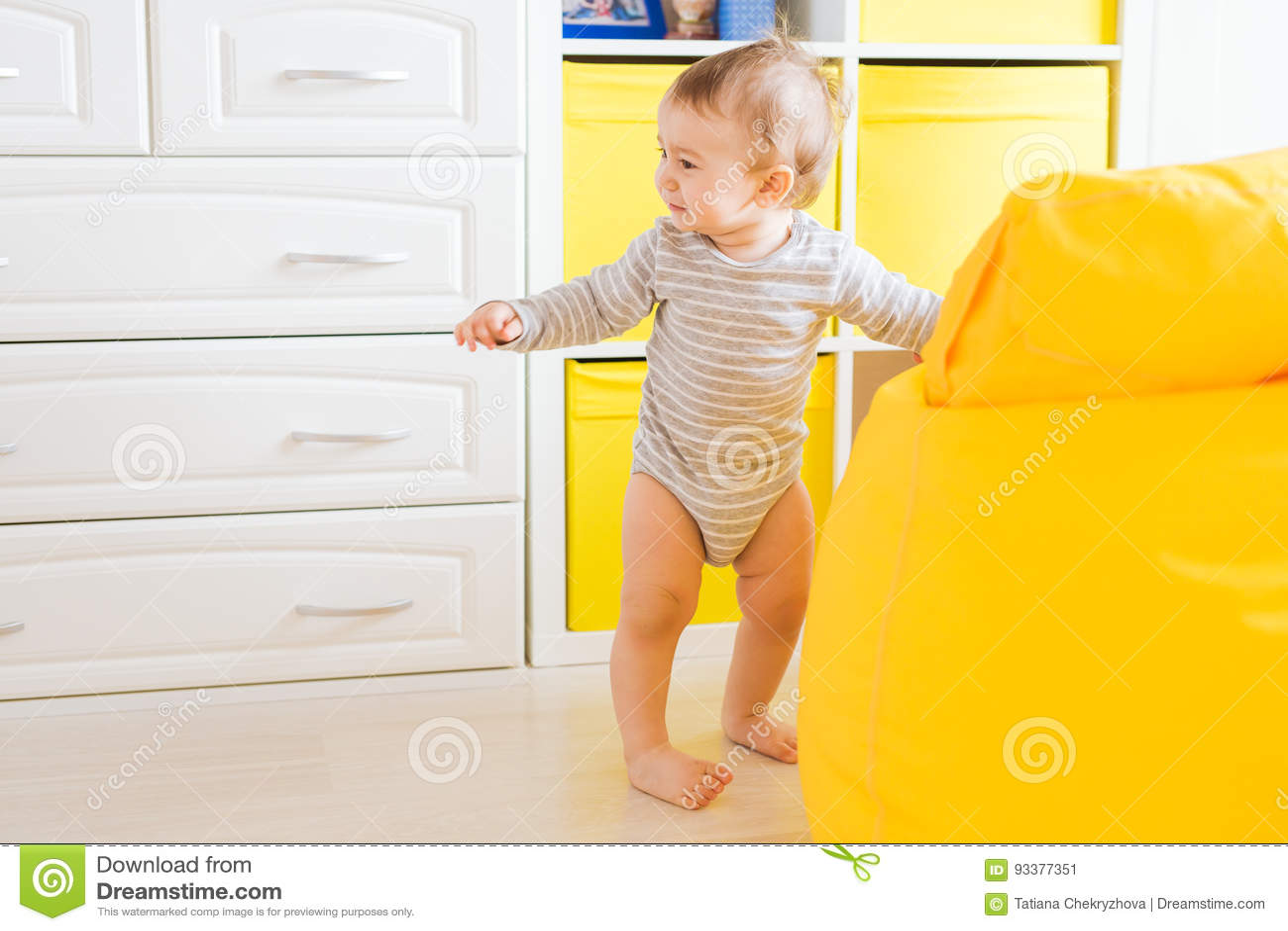 Nettes glückliches lachendes Baby, das auf weißem Schlafzimmer spielt