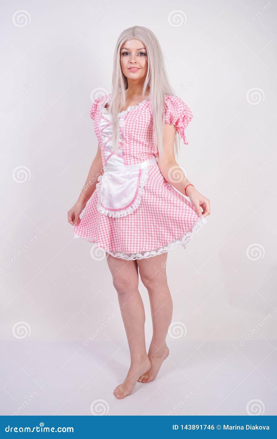Nettes junges kaukasisches jugendlich Mädchen im bayerischen Kleid des Rosaplaids mit dem Schutzblech, das auf festem Hintergrund