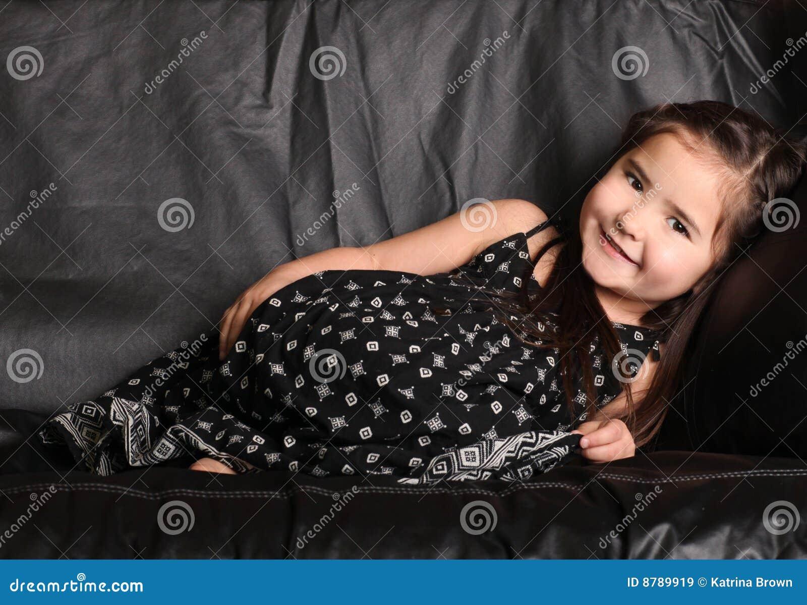 Nettes junges Kind, das auf einer Couch liegt
