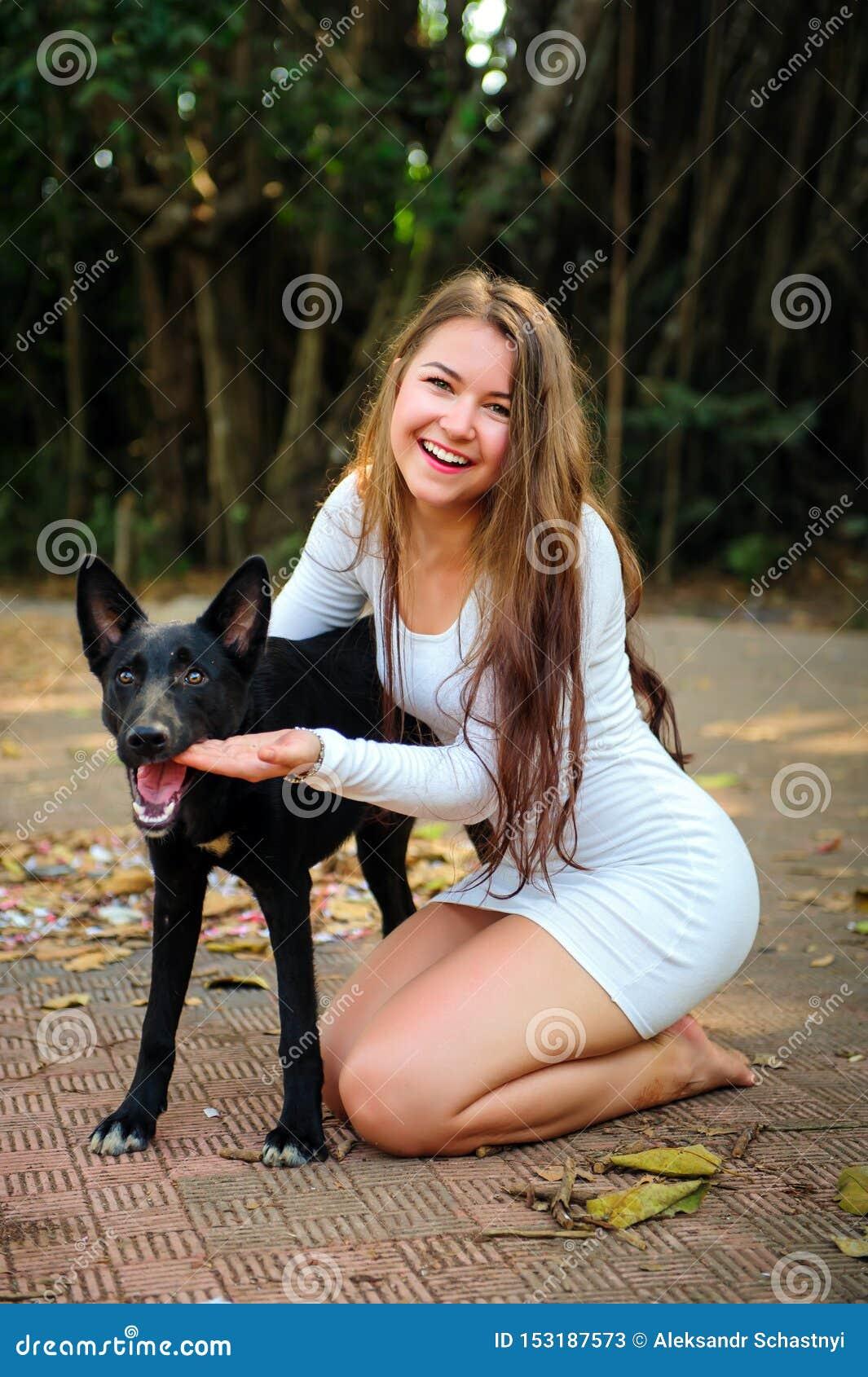 Nettes junges Mädchen auf Weg im Park mit ihrem Vierbeiner Hübsche Frau im kurzen Kleid und schwarzen im Hund, die draußen spielt