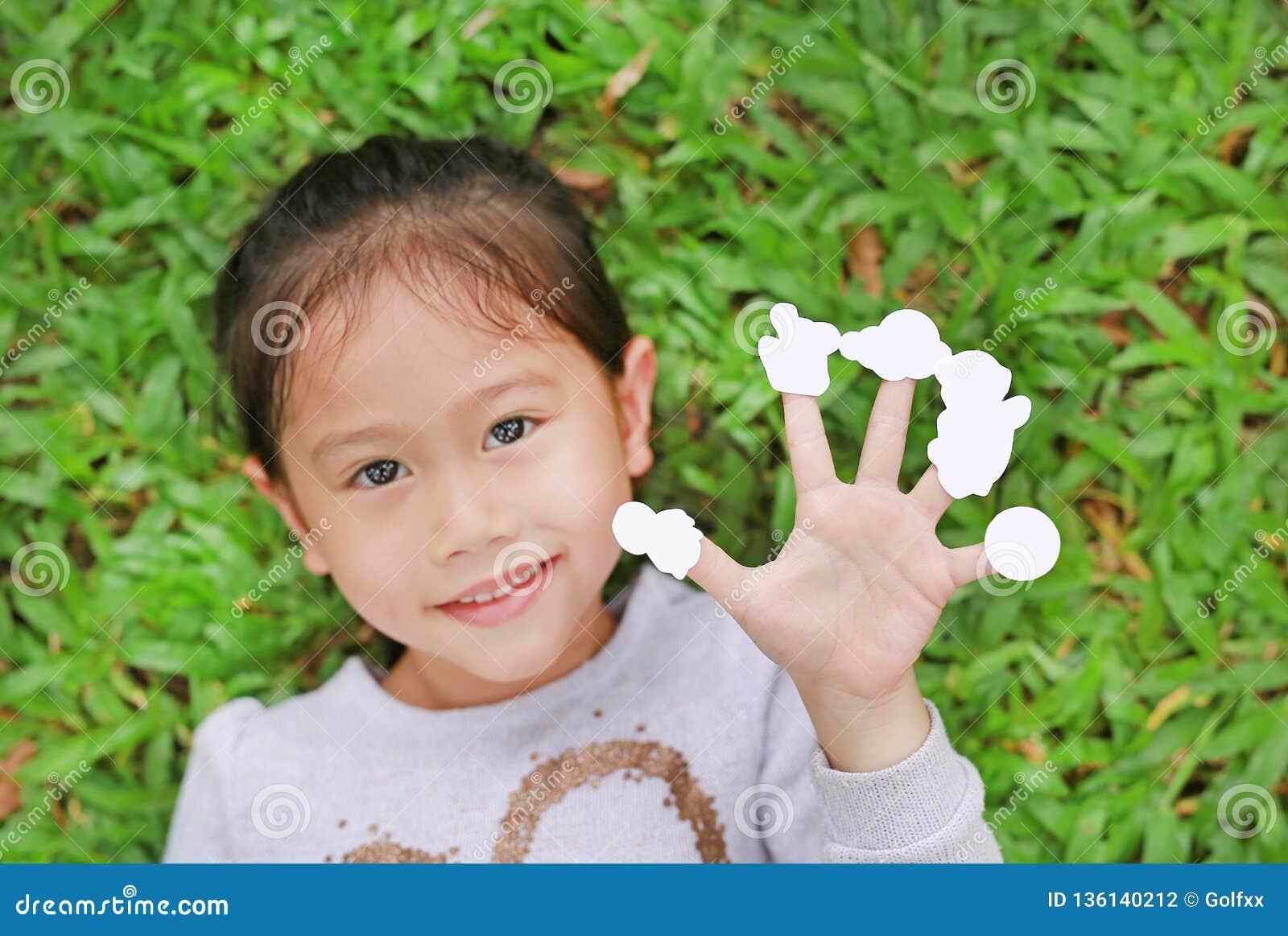 Nettes kleines asiatisches Kindermädchen, das auf Rasen des grünen Grases mit leeren weißen Aufklebern der Vertretung auf ihren F