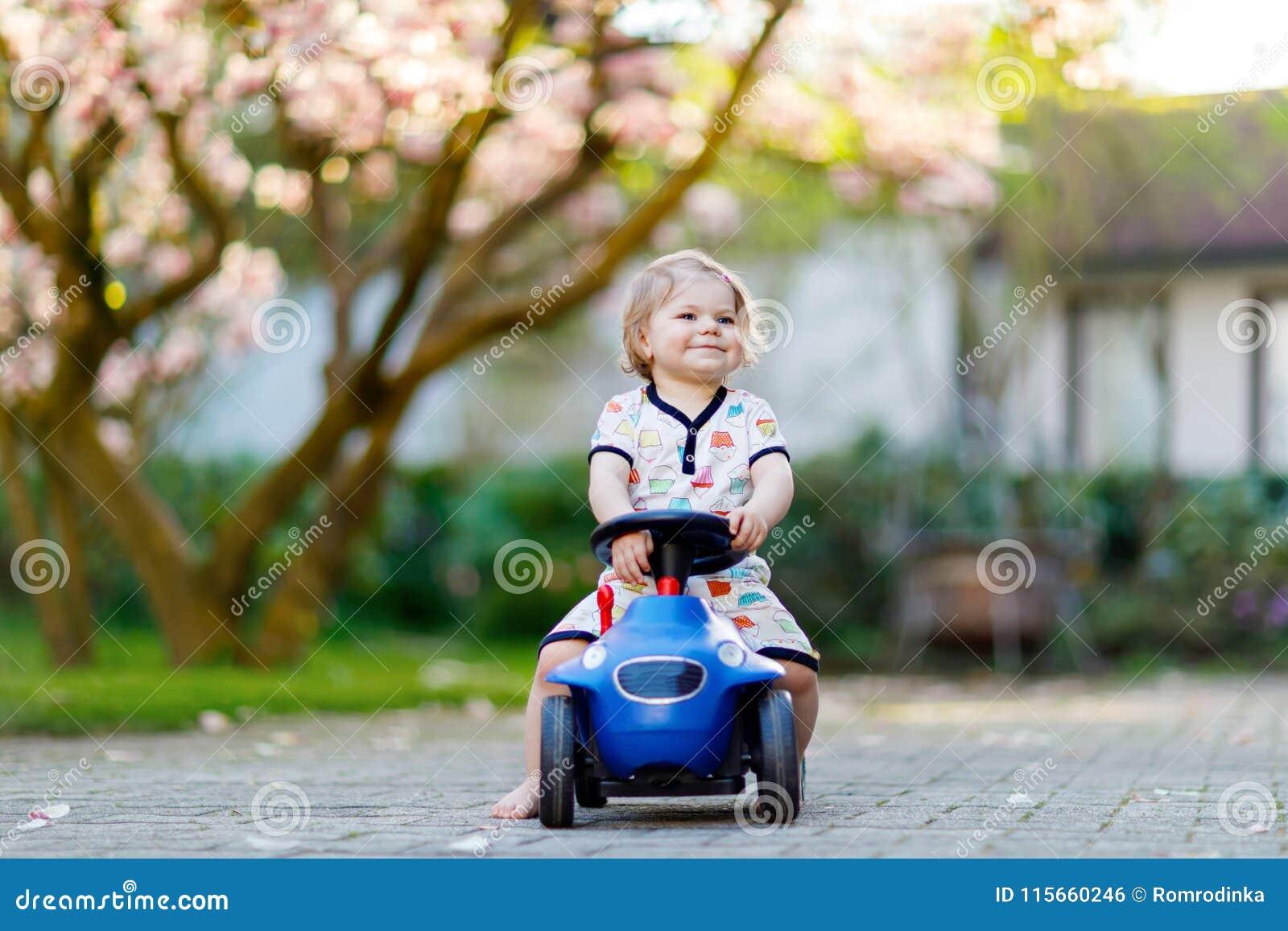 Nettes kleines Baby, das mit blauem kleinem Spielzeugauto im Garten des Hauses oder der Kindertagesstätte spielt Entzückendes sch