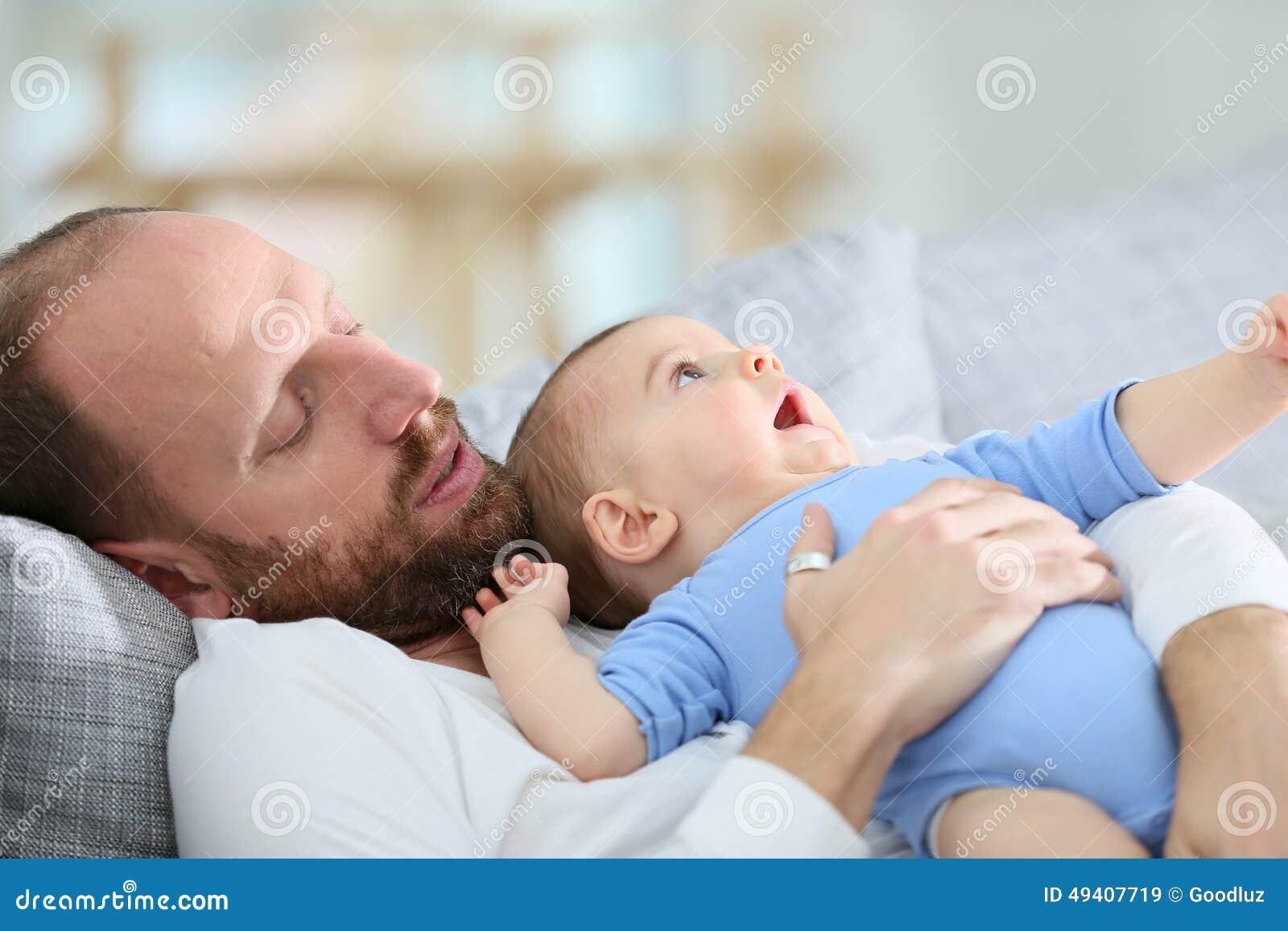 Download Nettes Kleines Baby In Den Armen Seines Vaters, Der Auf Dem Sofa Liegt Stockbild - Bild von erwachsener, gesichter: 49407719