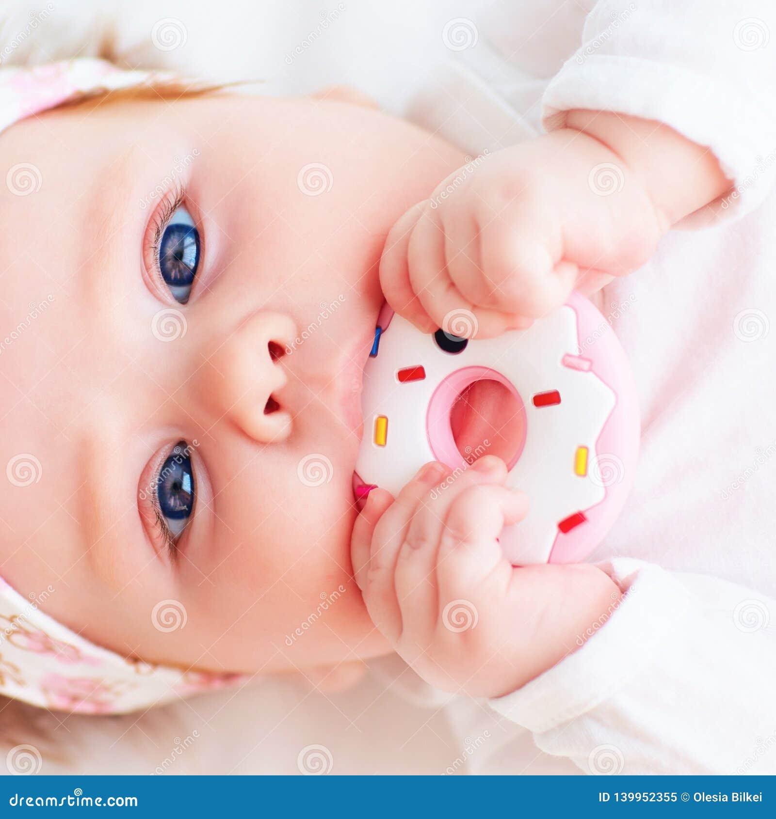 Nettes kleines Baby nagen ein Silikondonut teether ab