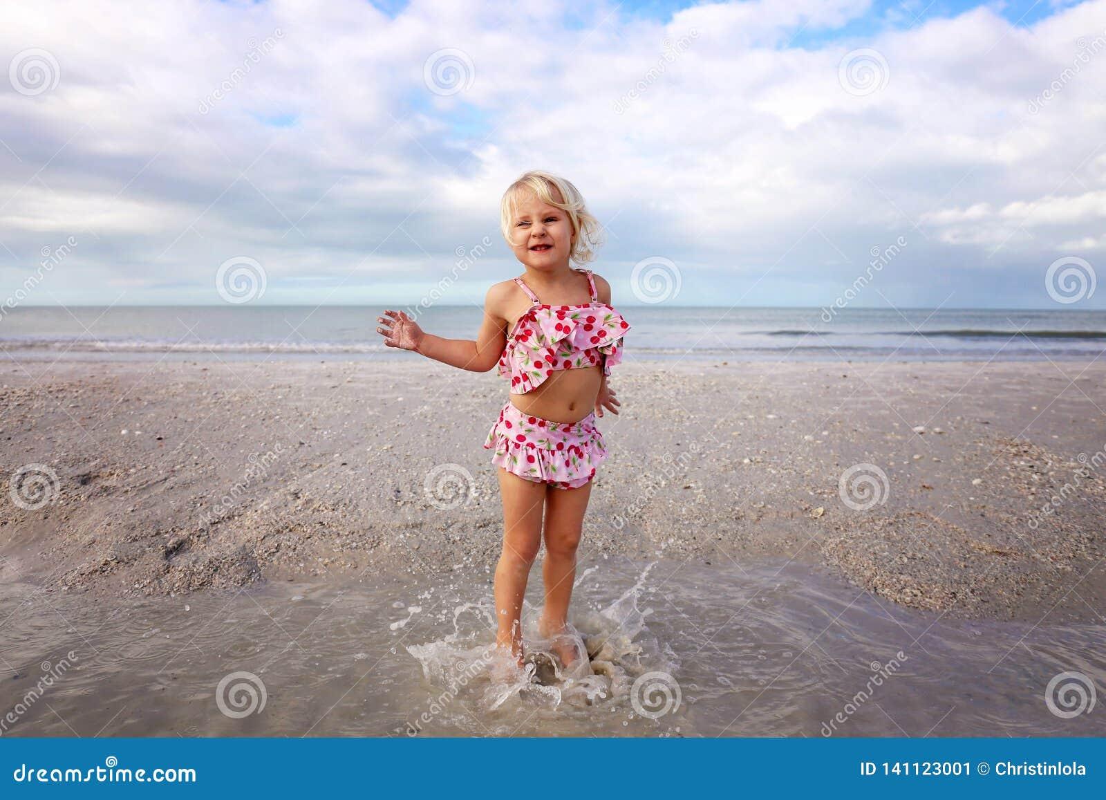 Nettes kleines Kind, das im Wasser auf dem Strand durch den Ozean spritzt und spielt