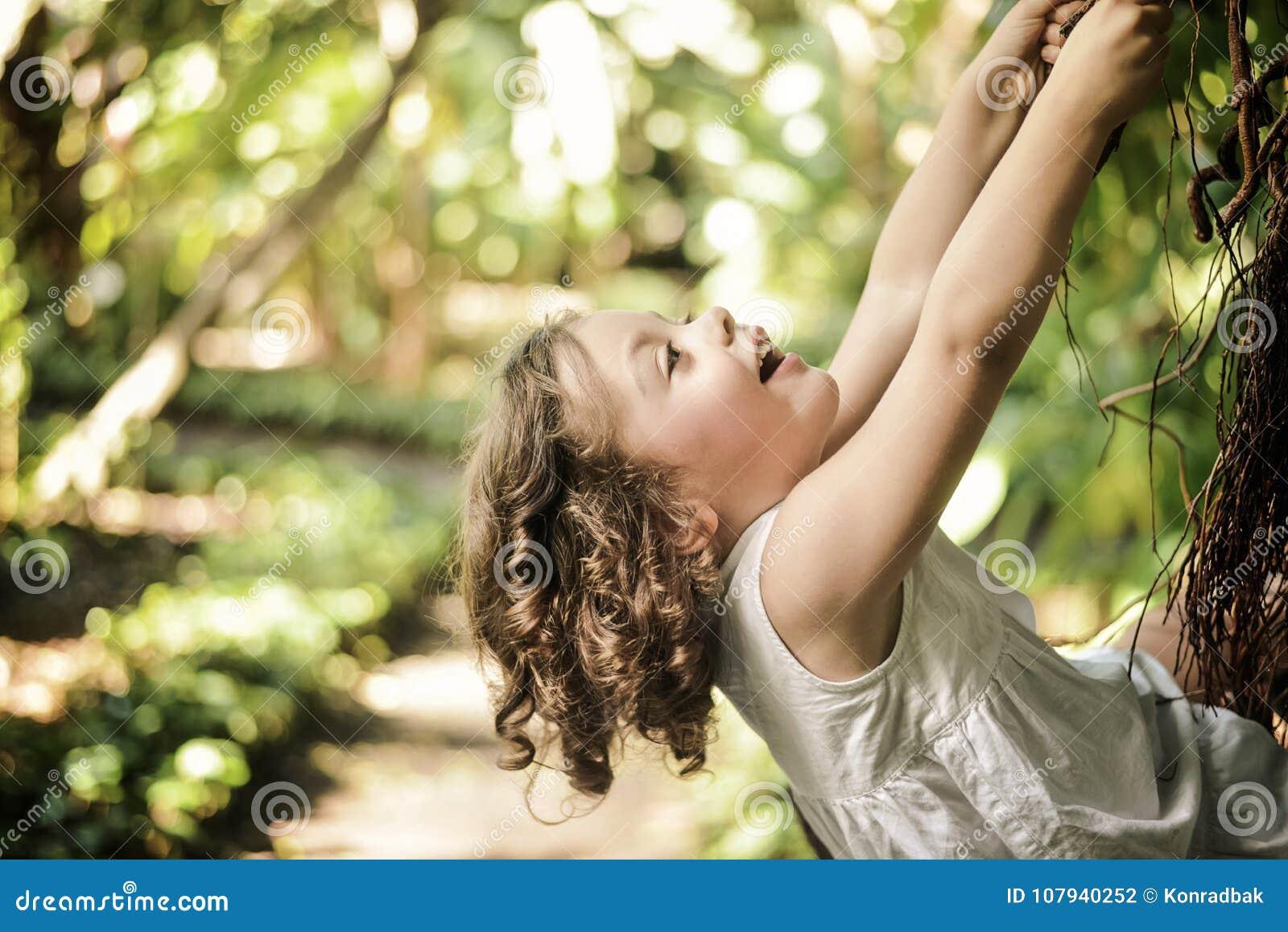 Nettes, kleines Mädchen, das auf einer Palme klettert
